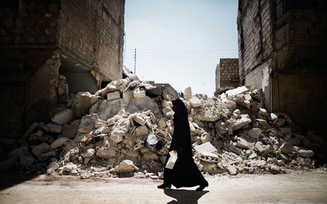 Φωτογραφίζοντας την καθημερινότητα του κόσμου - Μια γυναίκα περνάει μπροστά από κατεστραμμένο κτίριο στη Συρία