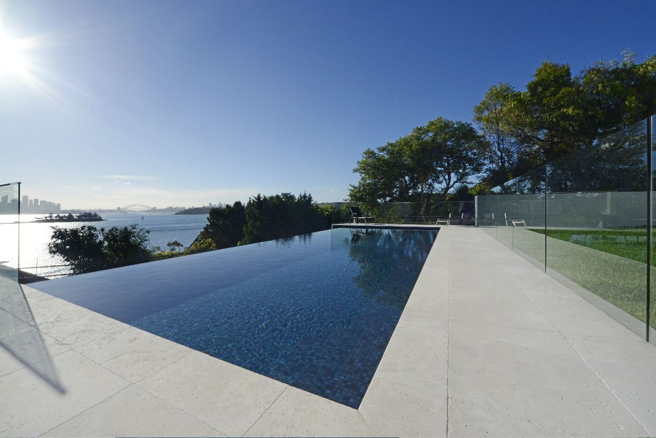 Modern infinity edge pool with glass fences swimming for Infinity pool design uk