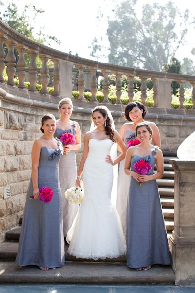 e75af3b8a27 Bridesmaids in gray gowns with stunning hot pink bouquets. Bride is wearing  Monique.