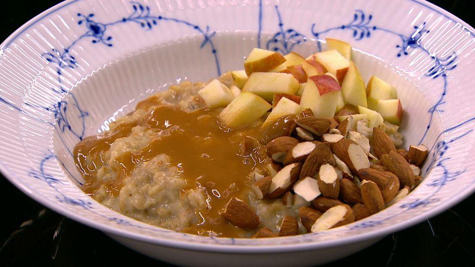 Havregrød med hjemmerørt dulce de leche (karamelsauce), frisk æble og ristede mandler er en lækker opskrift fra Go' morgen Danmark, se flere snacks på mad.tv2.dk