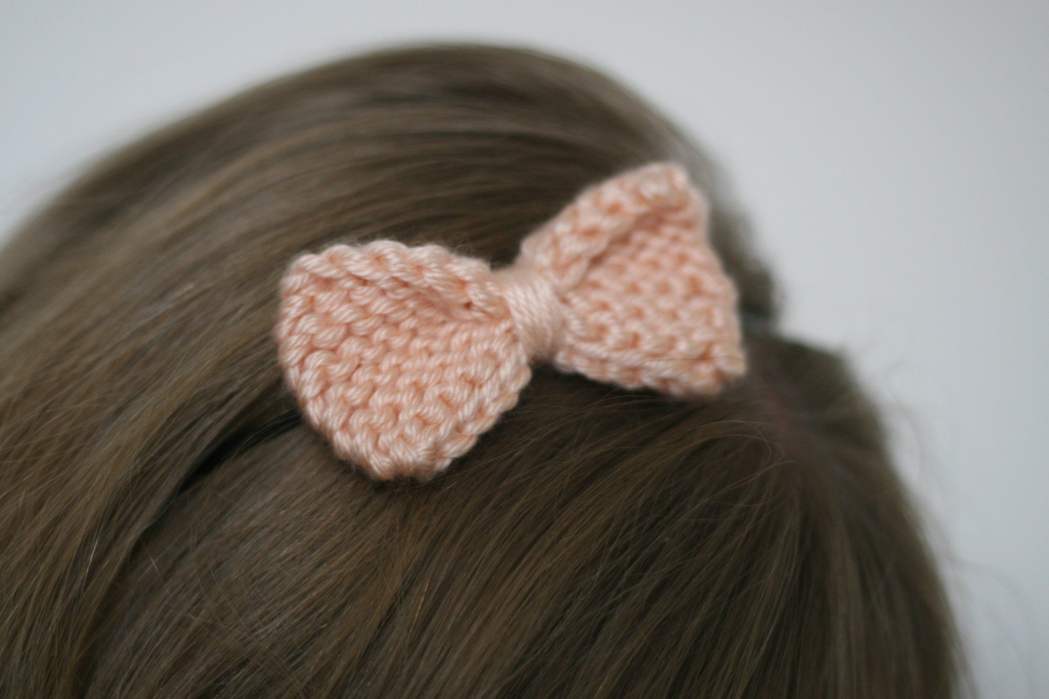 The knit bow is fastened to a black metal headband it easily fits