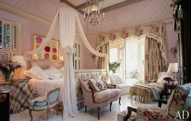 """A space Buatta proclaimed """"a fantasy room,"""" this master bedroom in the American Midwest is part of an English country–style house commissioned by architects Ferguson & Shamamian.  The lit à la polonaise is hung with panels of a Colefax and Fowler fabric held fast by tasseled tiebacks."""