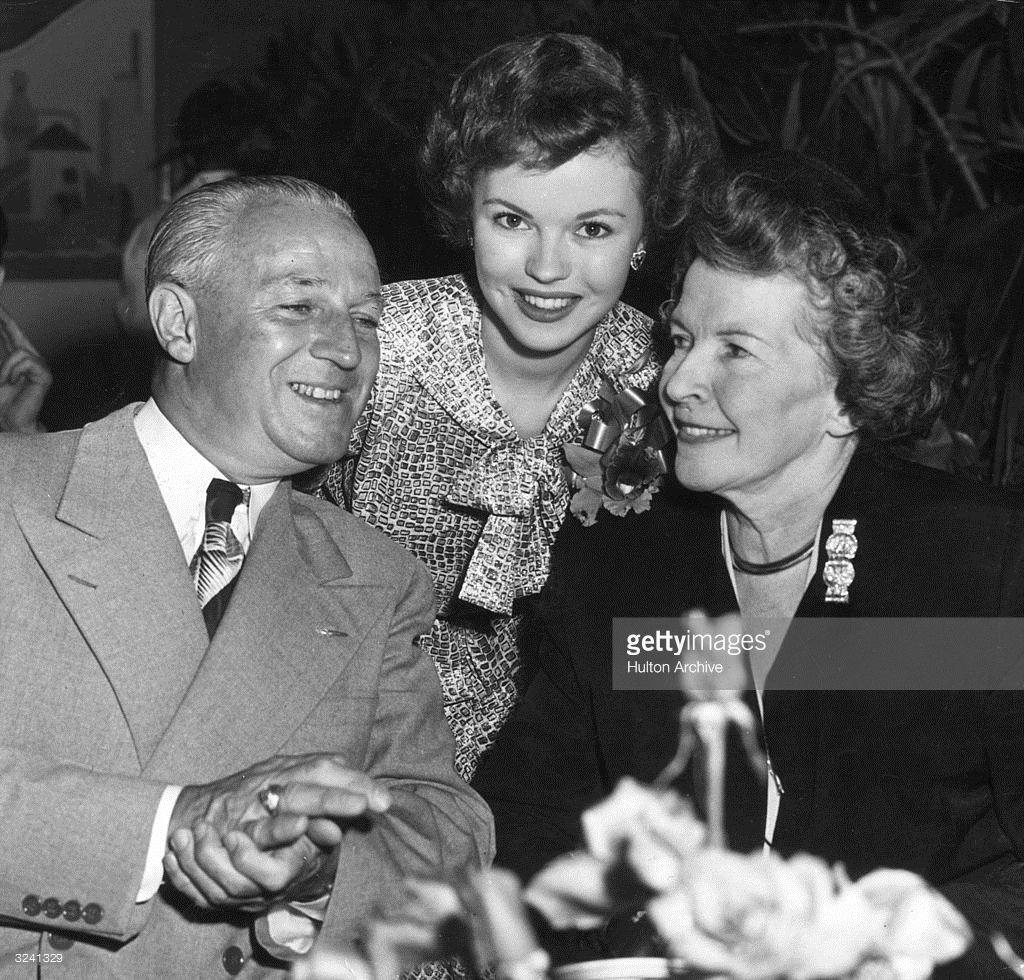American child actor Shirley Temple smiles while posing with her... #hollywoodactor
