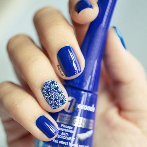 Cute looking dark blue nail art design. The blues are joined by a special nail design that consists of small light blue beads on top of dark blue background.