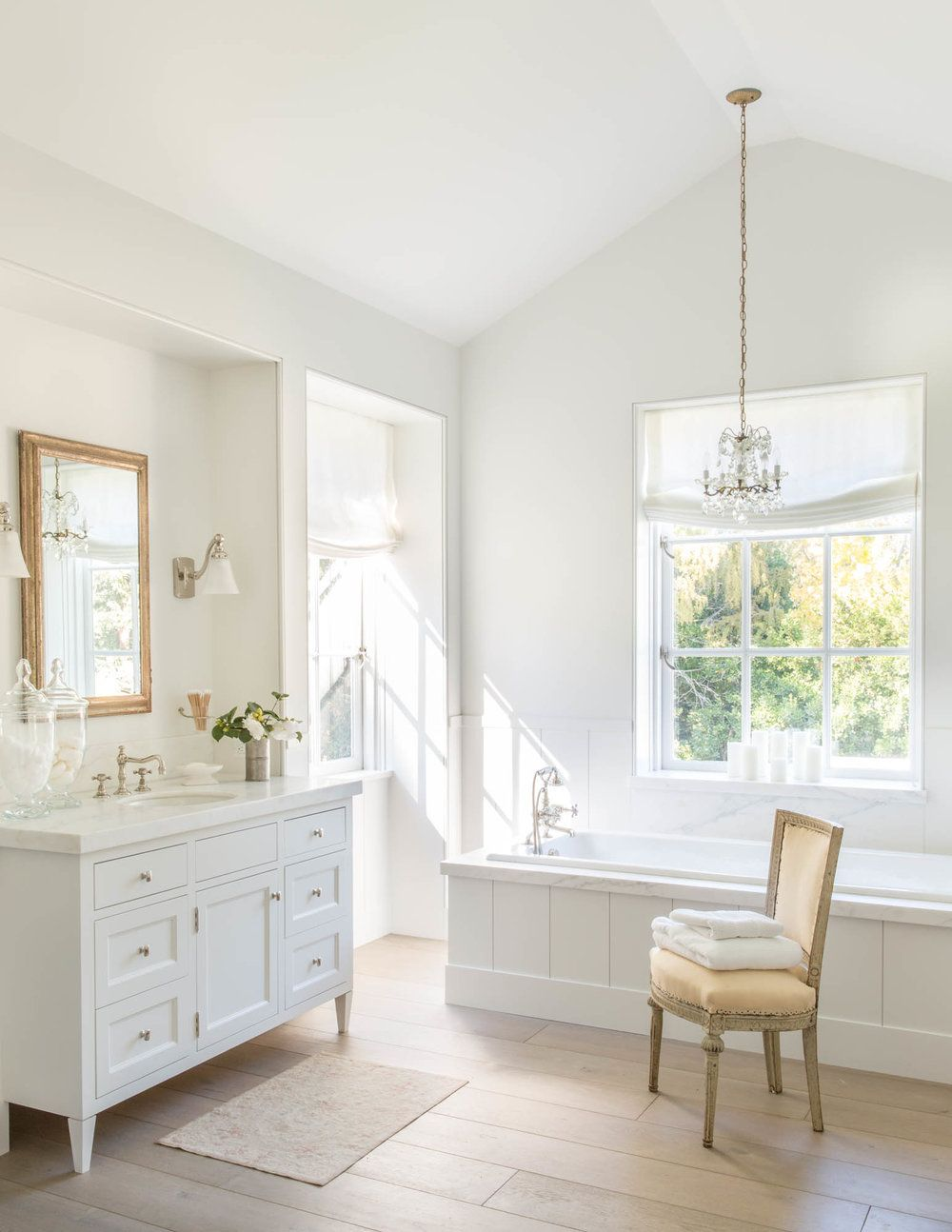 pictures to hang in master bathroom%0A Chic bathroom features a mini crystal chandelier hanging over a wainscoted  bathtub accented with a marble deck placed under a window dressed in a  white