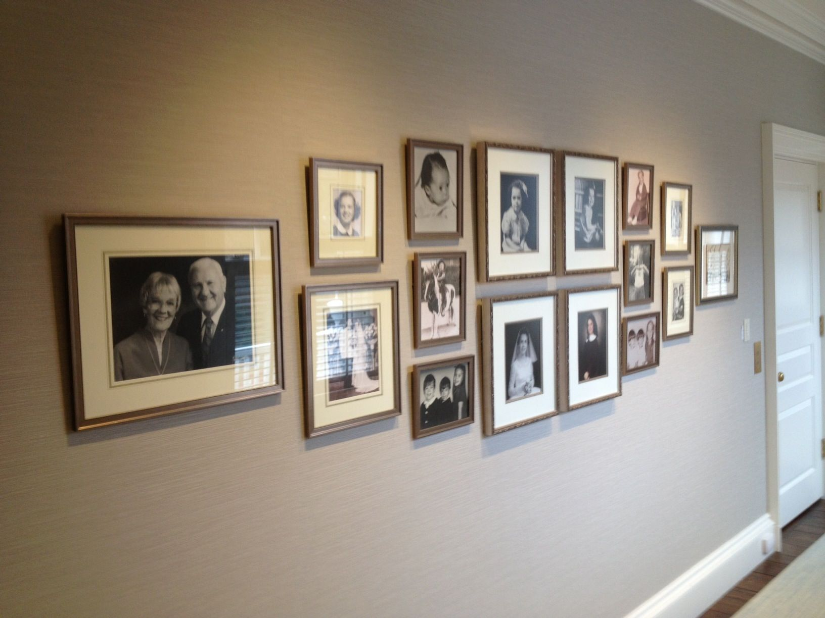 A Symmetrical Arrangement Of Family Photos On A Neutral Wall