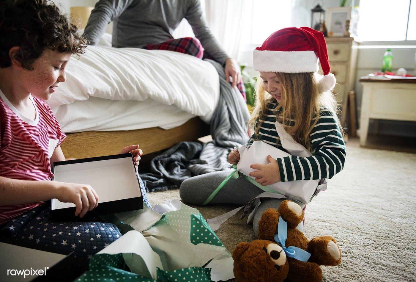 Download premium image of Caucasian siblings unwrapping Christmas