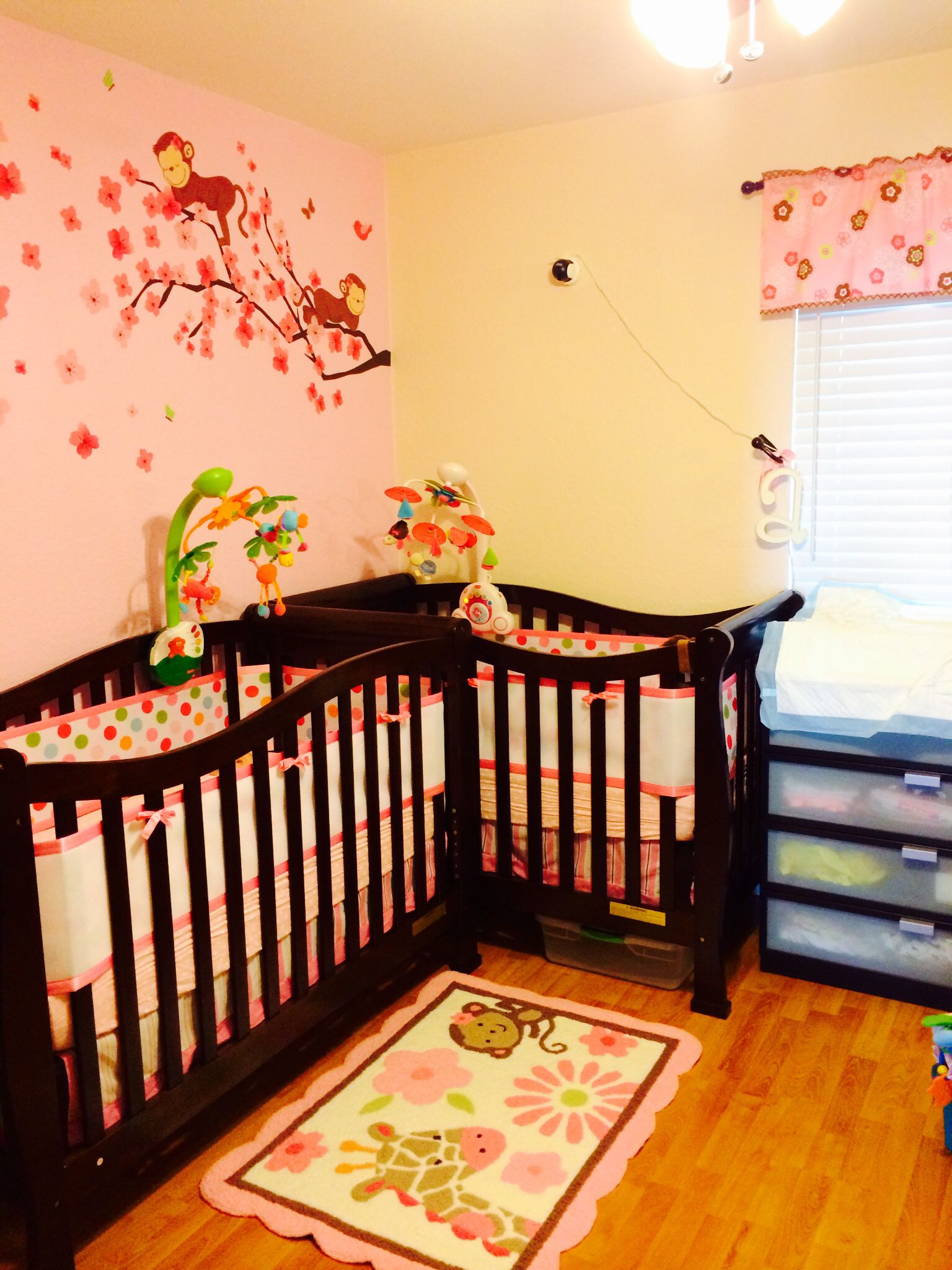 Twin girl nursery in a small room l shape monkey themed for Nursery room ideas for small rooms