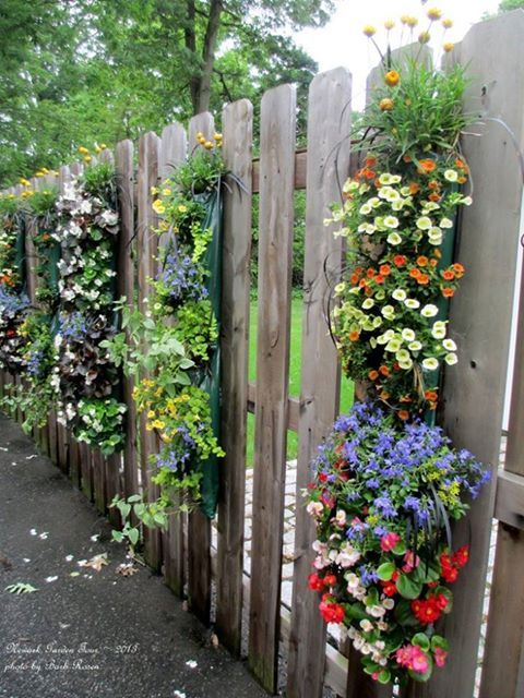 Hanging Planting Bags Filled With Annuals On Garden Fence.