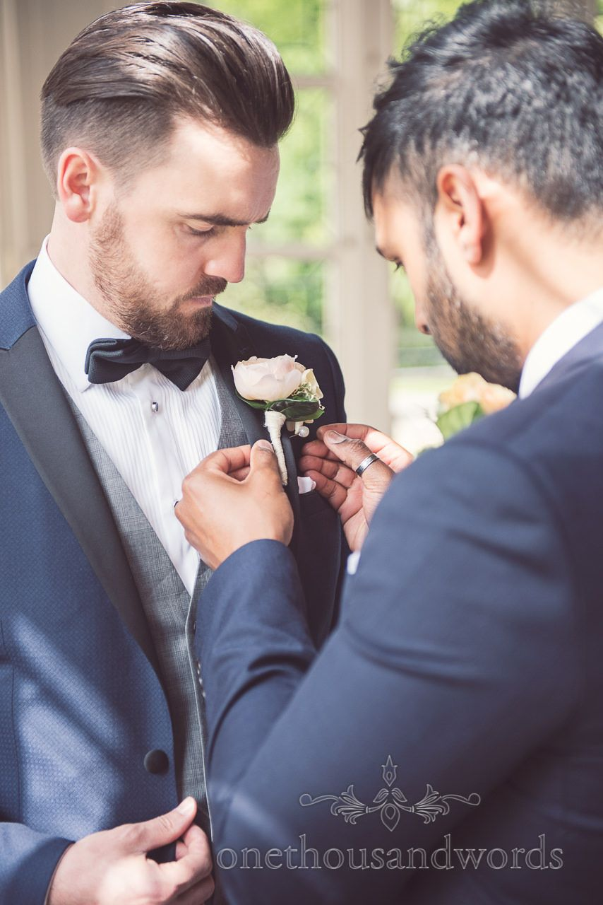 Groom in Bow Tie has button hole added by Best Man at