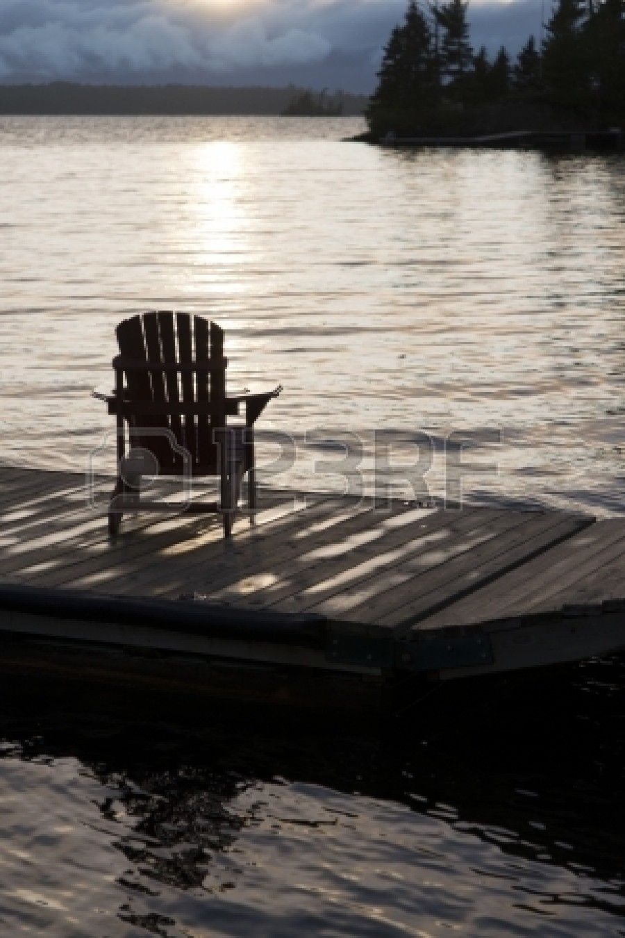 Colourful Adirondack Chairs On A Dock Stock Photo