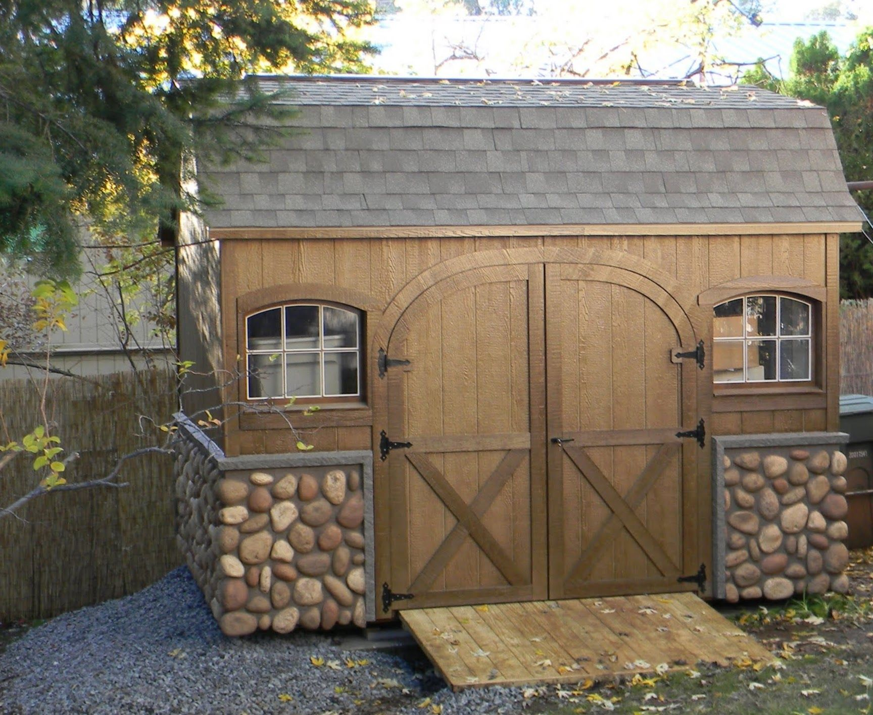 Dutch Colonial Storage Shed with Stone Veneer and Rounded Door
