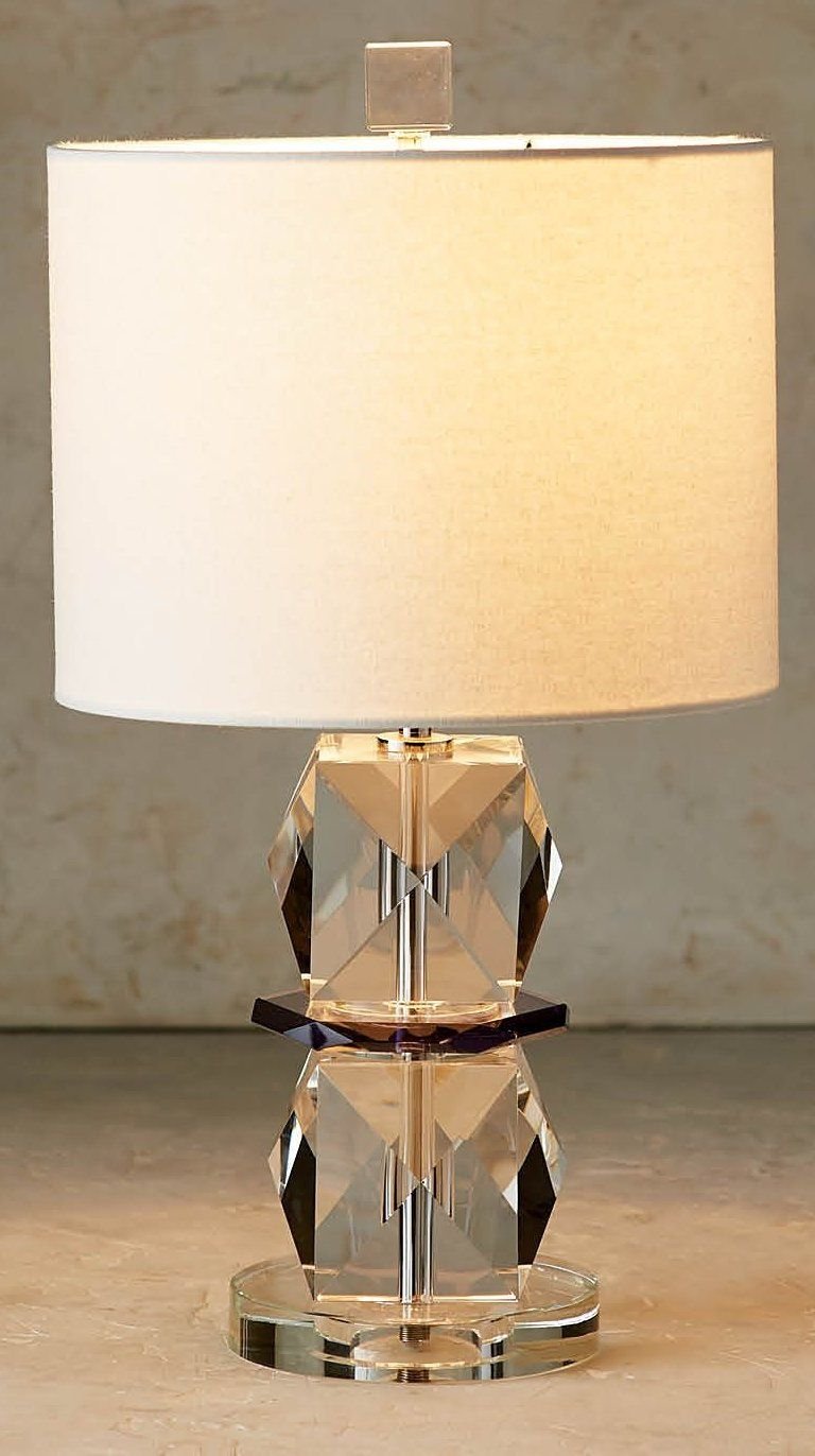 This sculptural table lamp features a clear glass crystal