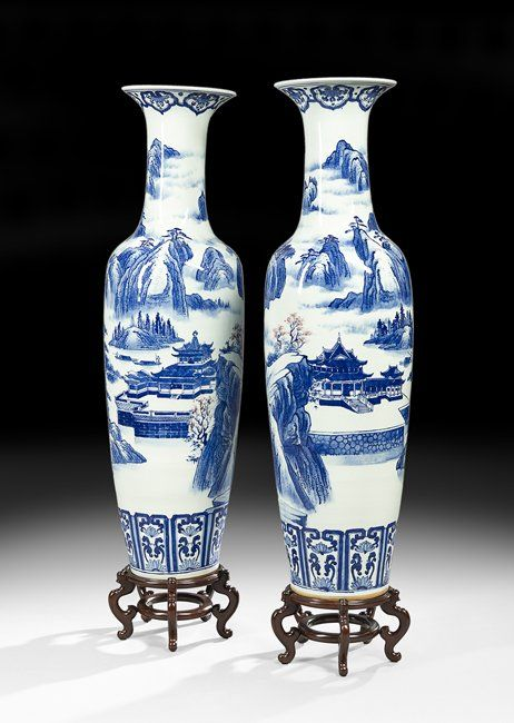 "Pair of Chinese Porcelain Palace Vases on Stands 20th century, each monumental amphora-form vase with a landscape scene of a palace situated among mountains rendered in blue and white with red accents on flowering prunus trees, unmarked, on carved wooden stands, h. 53-1/2"", dia. 15"", without stand."