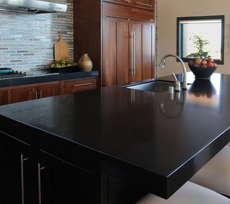 Black Quartz Countertops With A Blue Recycled Glass Island