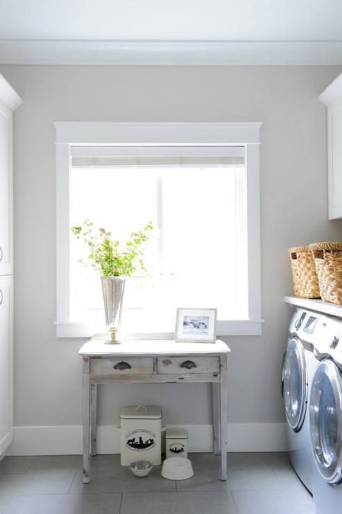 Gray laundry room features a pet food bowls tucked under a gray distressed farmhouse console table situated below a window flanked by tall cabinets to the left and a silver front load washer and dryer to the right. #graylaundryrooms Gray laundry room features a pet food bowls tucked under a gray distressed farmhouse console table situated below a window flanked by tall cabinets to the left and a silver front load washer and dryer to the right. #graylaundryrooms