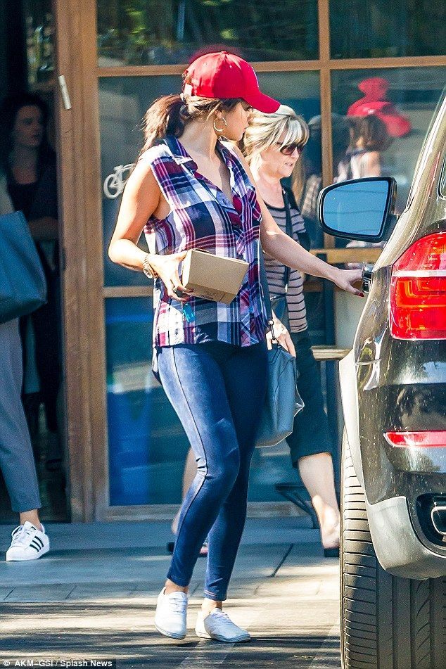 Sporty: Selena styled the loose-fitting, multi-tonal top with a pair of blue skinny jeans,...
