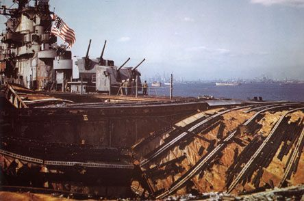 The USS Franklin's devastated flight deck is seen in this color photo, as she sails proudly under her own power to the Brooklyn Navy Yard in late April 1945. Two bombs that hit her on March 19, 1945 ignited fires that resulted in the most damage received by any Essex-class carrier in the war. Total casualties were 802 killed and 265 wounded.