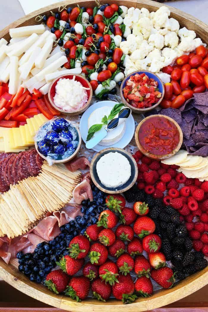 How to Make an Epic July 4th Charcuterie Board? Follow along for all the delicious red, white, and blue details for the best cheese board, ever! #reluctantentertainer #cheeseboard #charcuterie #holiday #july4 #charcuterieboard