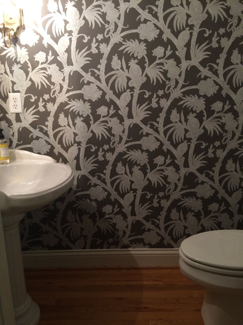 The white pedestal sink & toilet, wood floors and brass fixtures pop against the dark paper