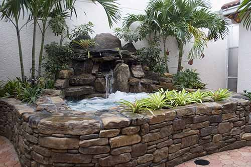 Waterfall With A Fieldstone Radius Retaining Wall In A Strip