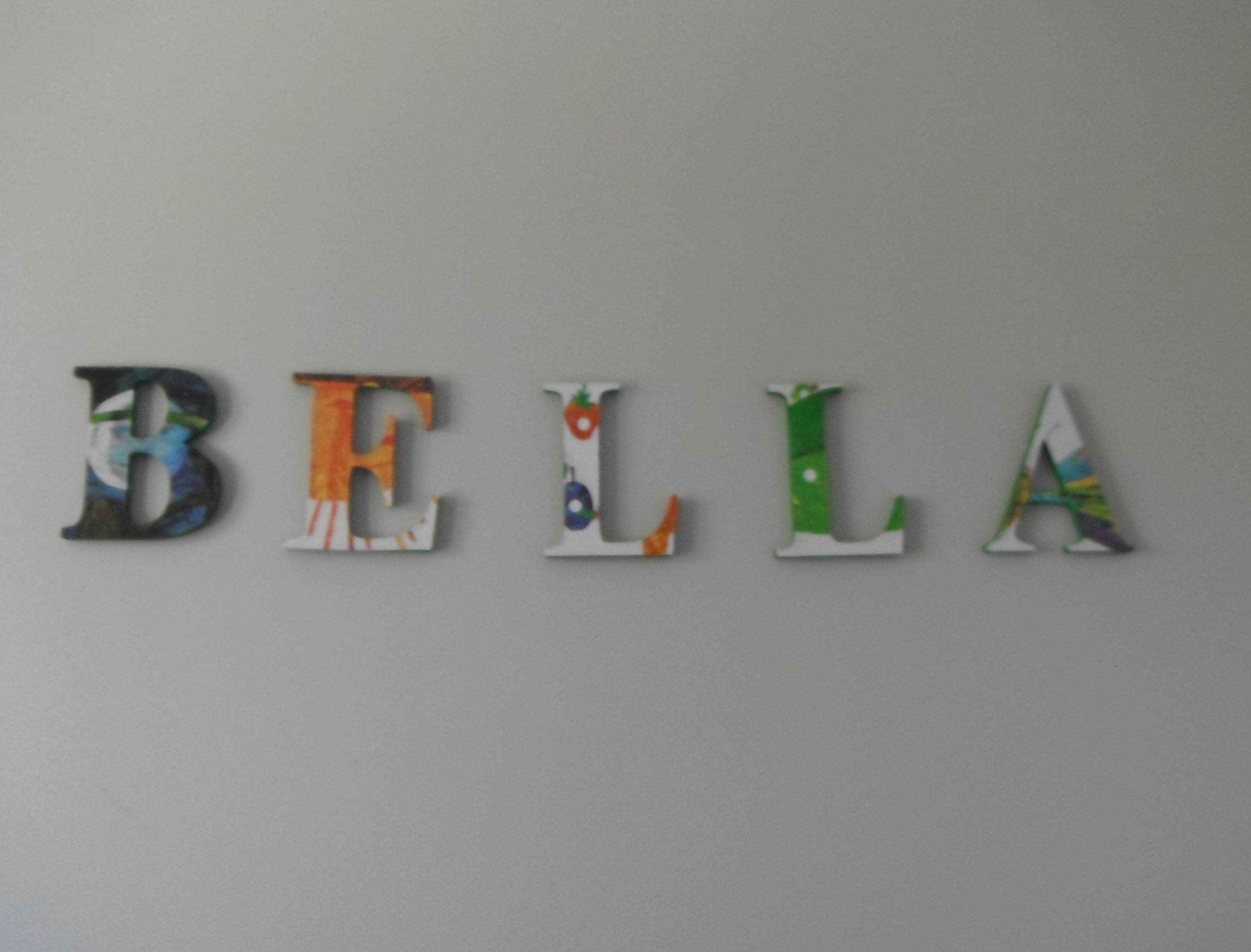 Hungry caterpillar name. I brought a second hand hungry caterpillar paper book and some wooden letters. I choose the pictures I wanted to use and traced the letters onto the picture. I painted the letters first - white on the front and green on the edges. I then cut out the pictures and mod podged them onto the letters.