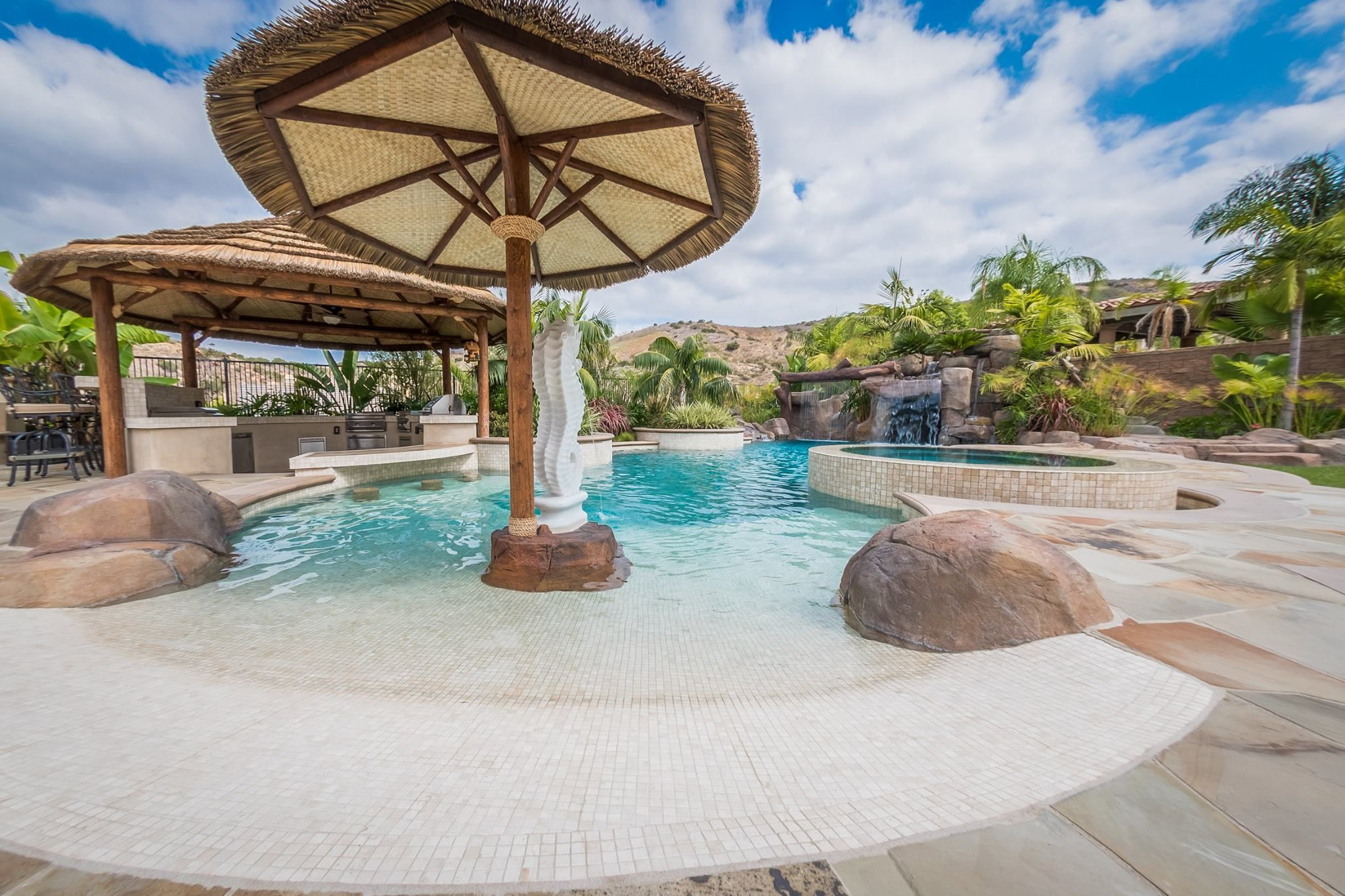 Materials Tropical Beach Entry Custom Swimming Pool With A Perimeter Flow Spa Grotto Rock Slide And Waterfalls Outdoor Kitchen Swim Up Bar