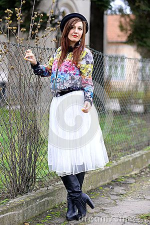 Beautiful young woman against fence.