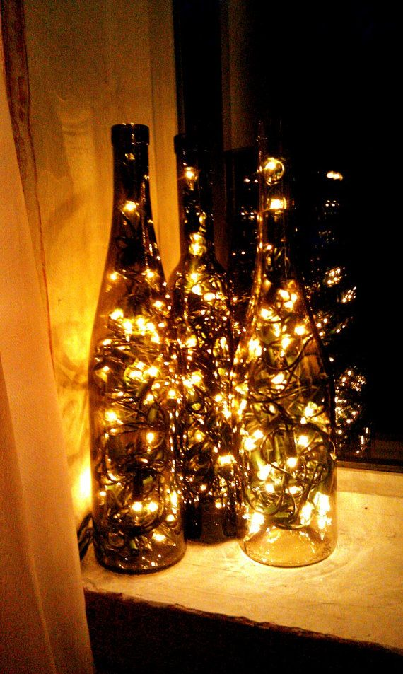 recycle an empty wine bottle by placing christmas lights inside and poof you got pretty and cute lighting diy