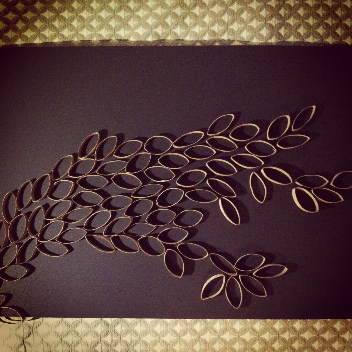 Homemade wall art made by using recycled paper towel rolls