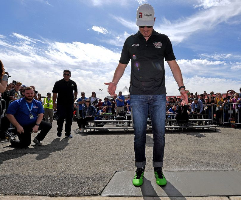 NASCAR driver Kyle Busch steps into fresh concrete on