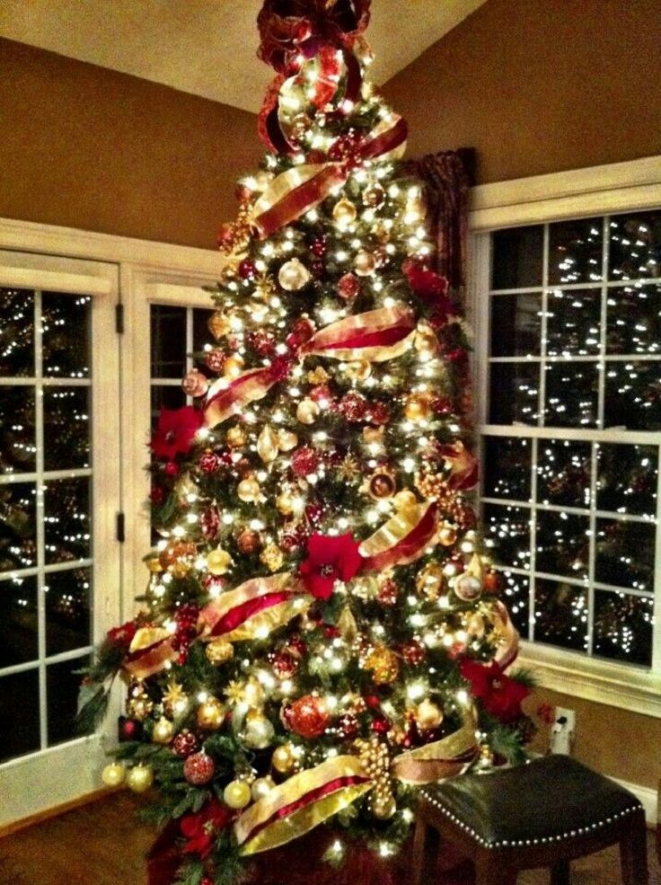 Top 10 Inventive Christmas Tree Themes-Love the bow on top with the ribbon  going around the tree (red & gold)