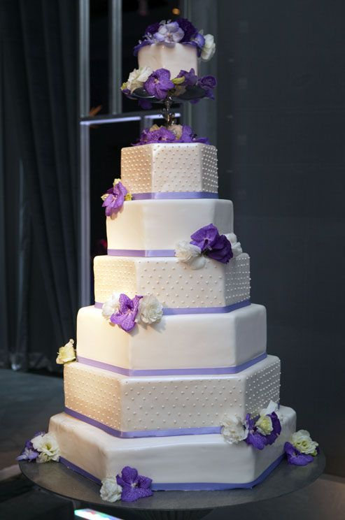 Swiss dots and fresh purple orchids and white lisianthus accent this seven-tiered wedding cake.