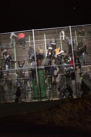 Imigrantes africanos escalam grade e forçam entrada na Europa .Santi Palacios/AP