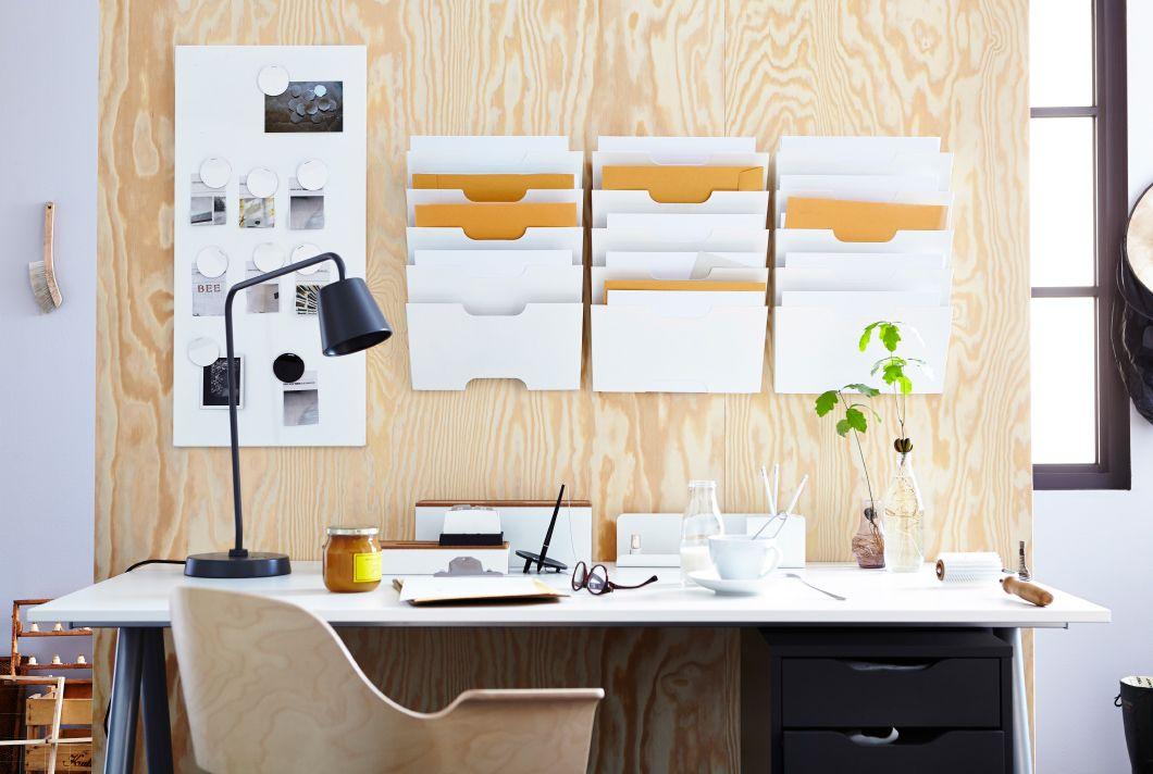 Skrivbord framför en träpanel med anslagstavla och väggfickor från IKEA.
