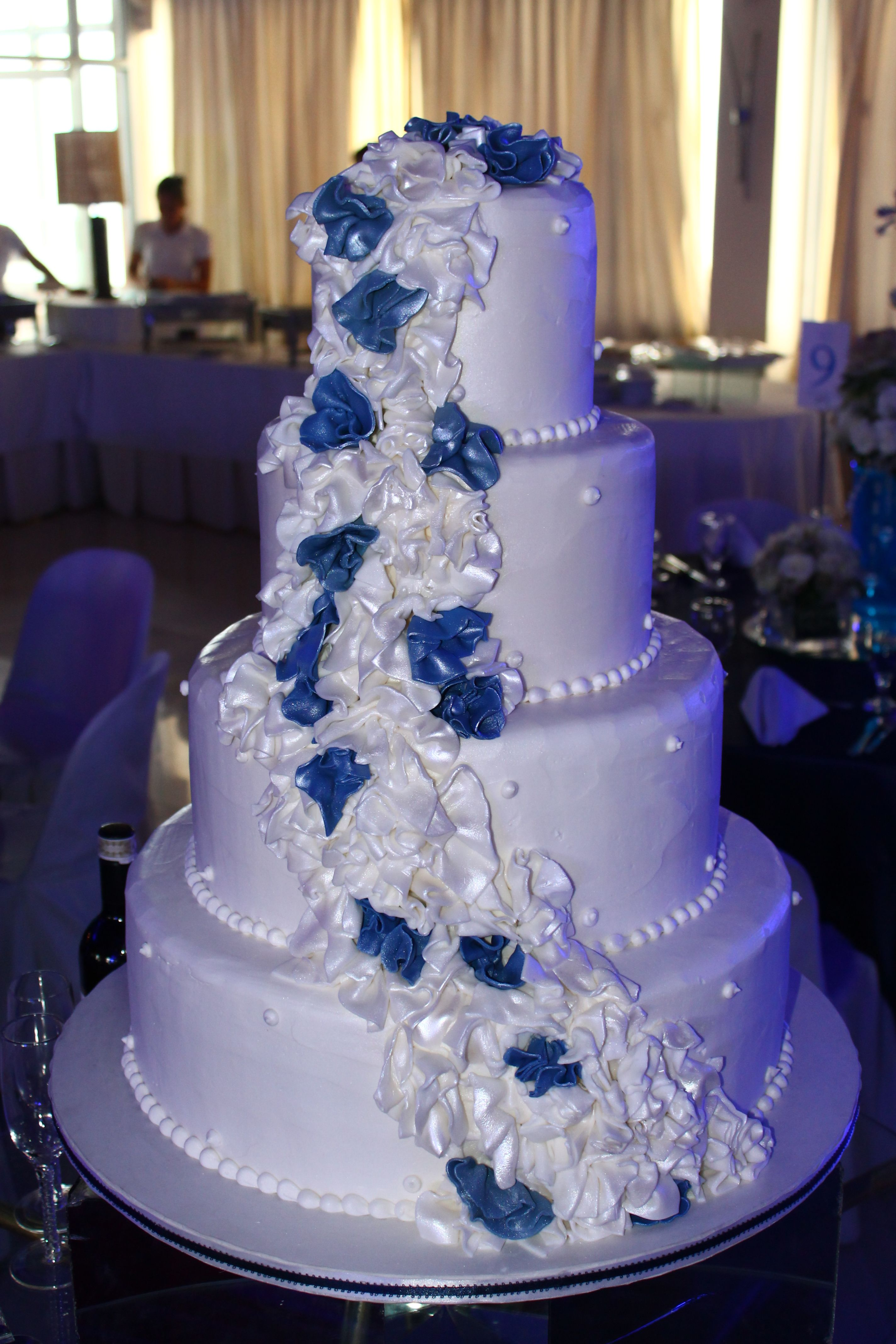4 layer white wedding cake with cascading white and navy blue