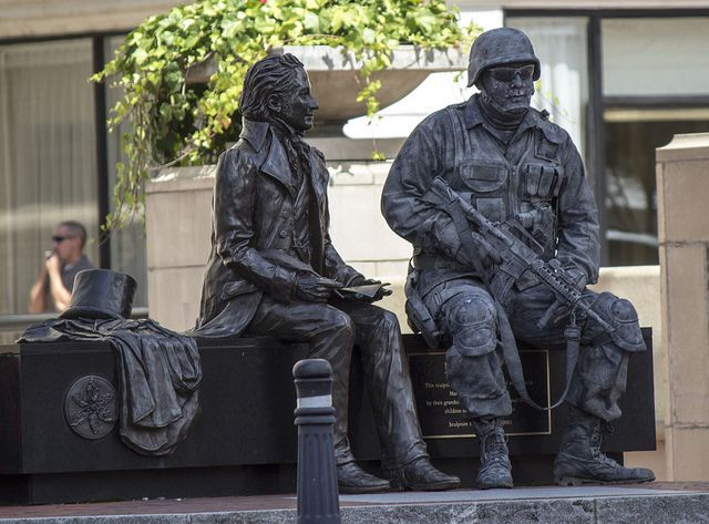 """We ran into this man last weekend while in Greenville, SC taking street shots. He was in full combat gear and made up to look like a statue and called himself """"The Stone Soldier"""". He took different poses and would remain absolutely still as if he were a statue.  I believe he may have been representing Disabled Veterans."""