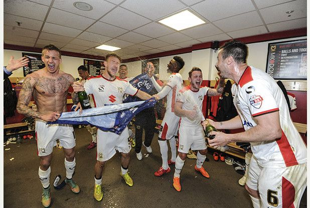 MK Dons celebrate in the dressing room and there will be some big teams to play in the Championship next season