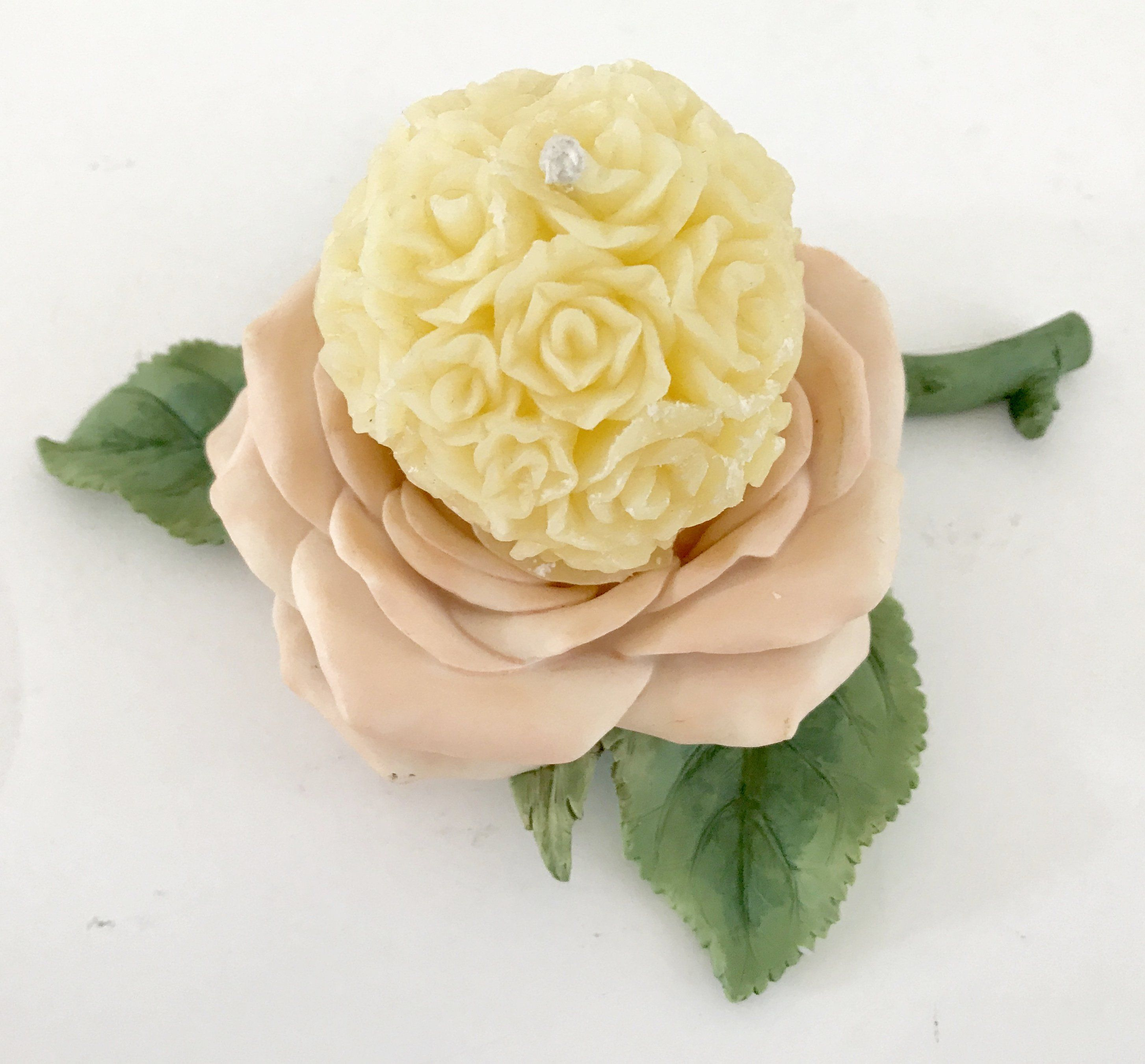 beeswax decorative floral candle resting on a ceramic pink rose