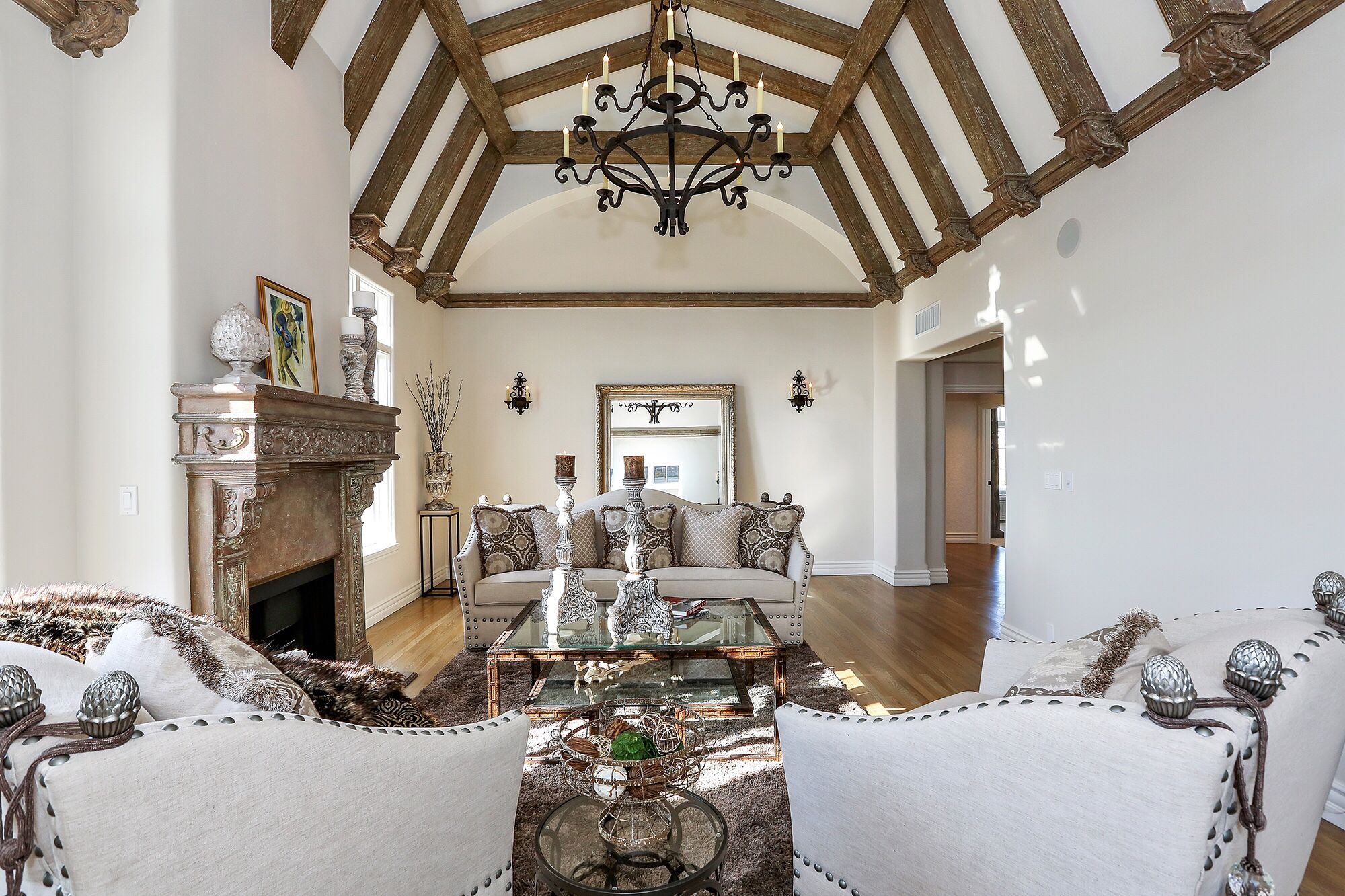 Gorgeous White Formal Living Room With A Vaulted Post And Beam Ceiling Featuring Hand Fo Rustic Living Room Design Rustic Living Room Wrought Iron Chandeliers #rustic #living #room #chandelier