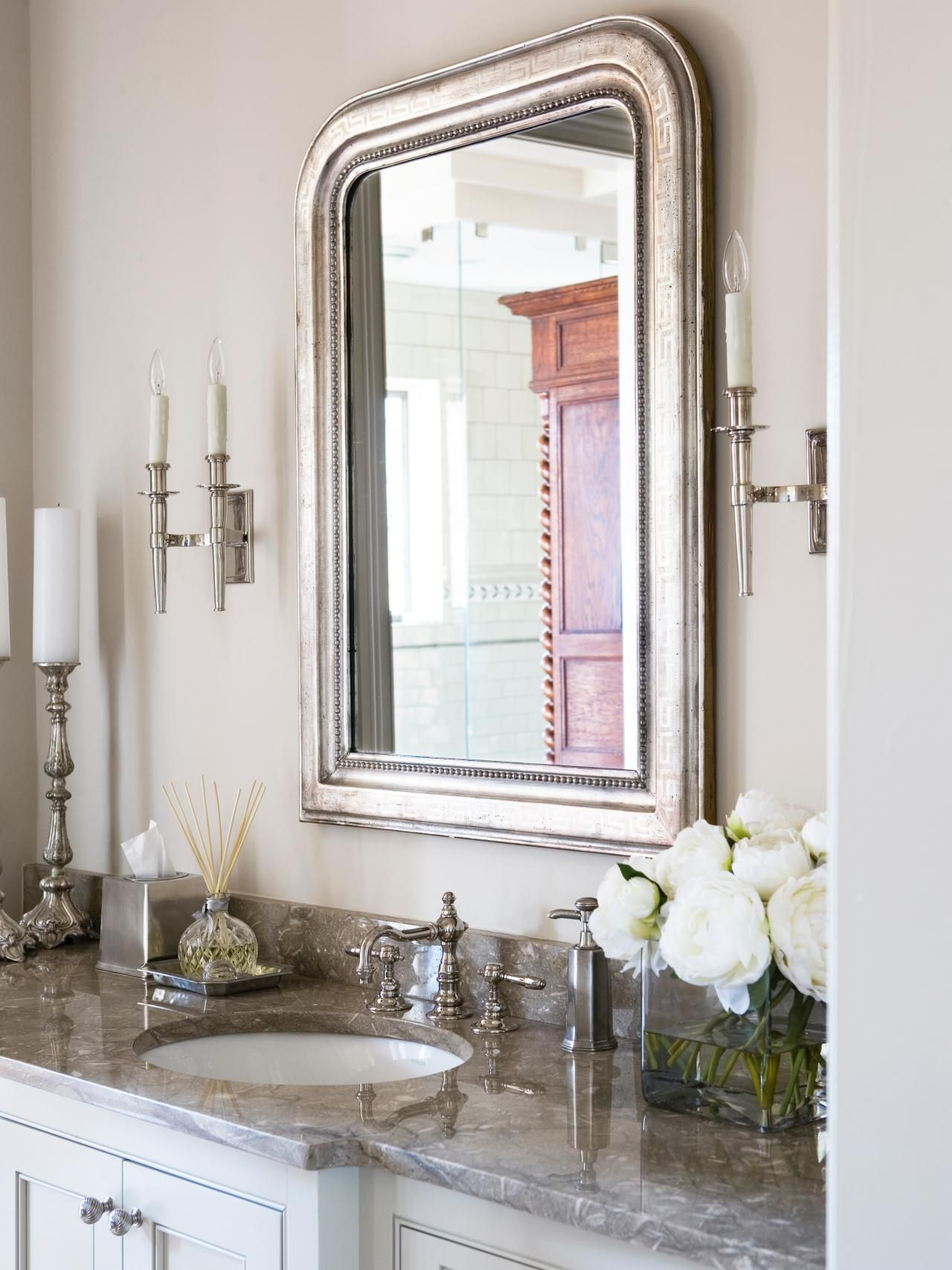An arched silver framed mirror is the eye catching centerpiece in ...