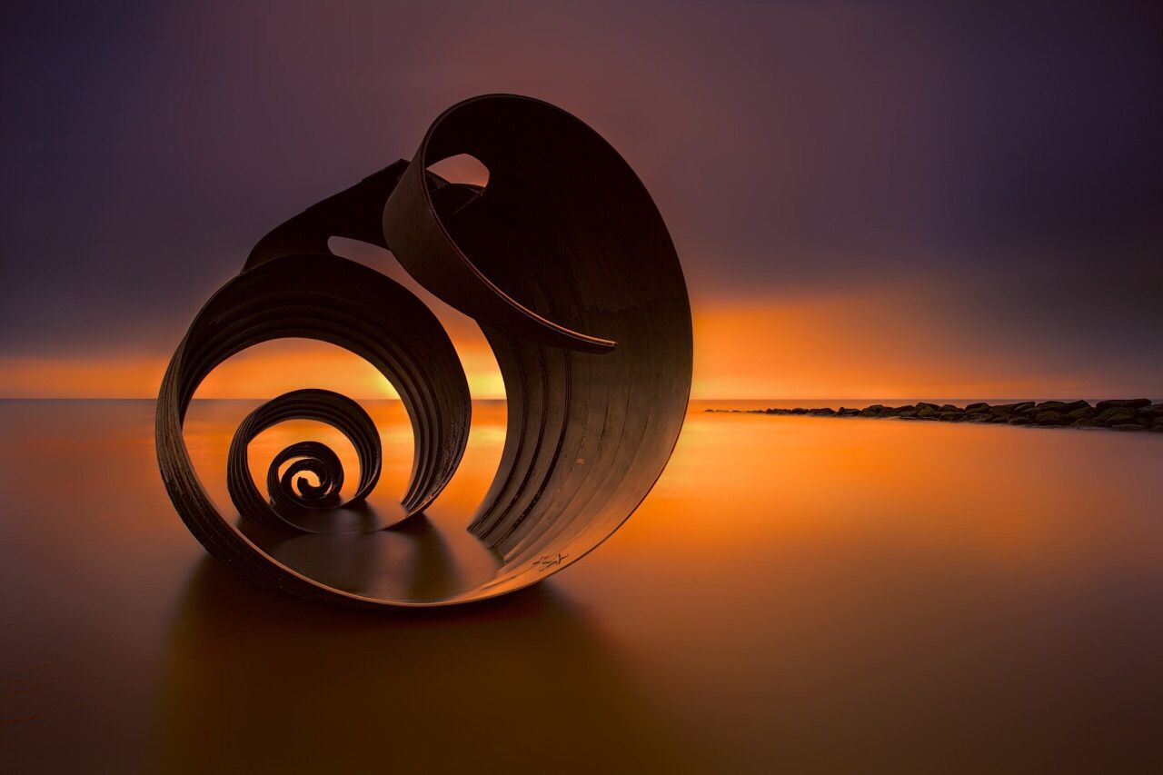 sunset and sea shell, by Shutterbug_UK Taken at Cleveleys on the North West Coast of the United Kingdom. This sculpture stands 4metres tall and weighs over 16 tonnes. It is completely covered at high tide