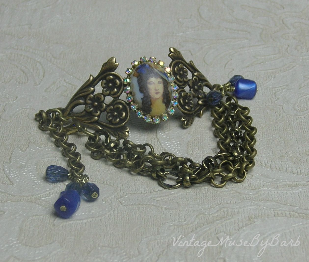 """FUF 05/19/17 """"Lady in a Blue Hat""""  Vintage cameo on brass ox cuff, triple chain, vintage moonglow Lucite beads, AB rhinestone cup chain, blue teardrop czech beads.  All from bsueboutiques, bsueboutiquesupplies on Etsy except clasp and Lucite beads.  By Barbara Kelley"""