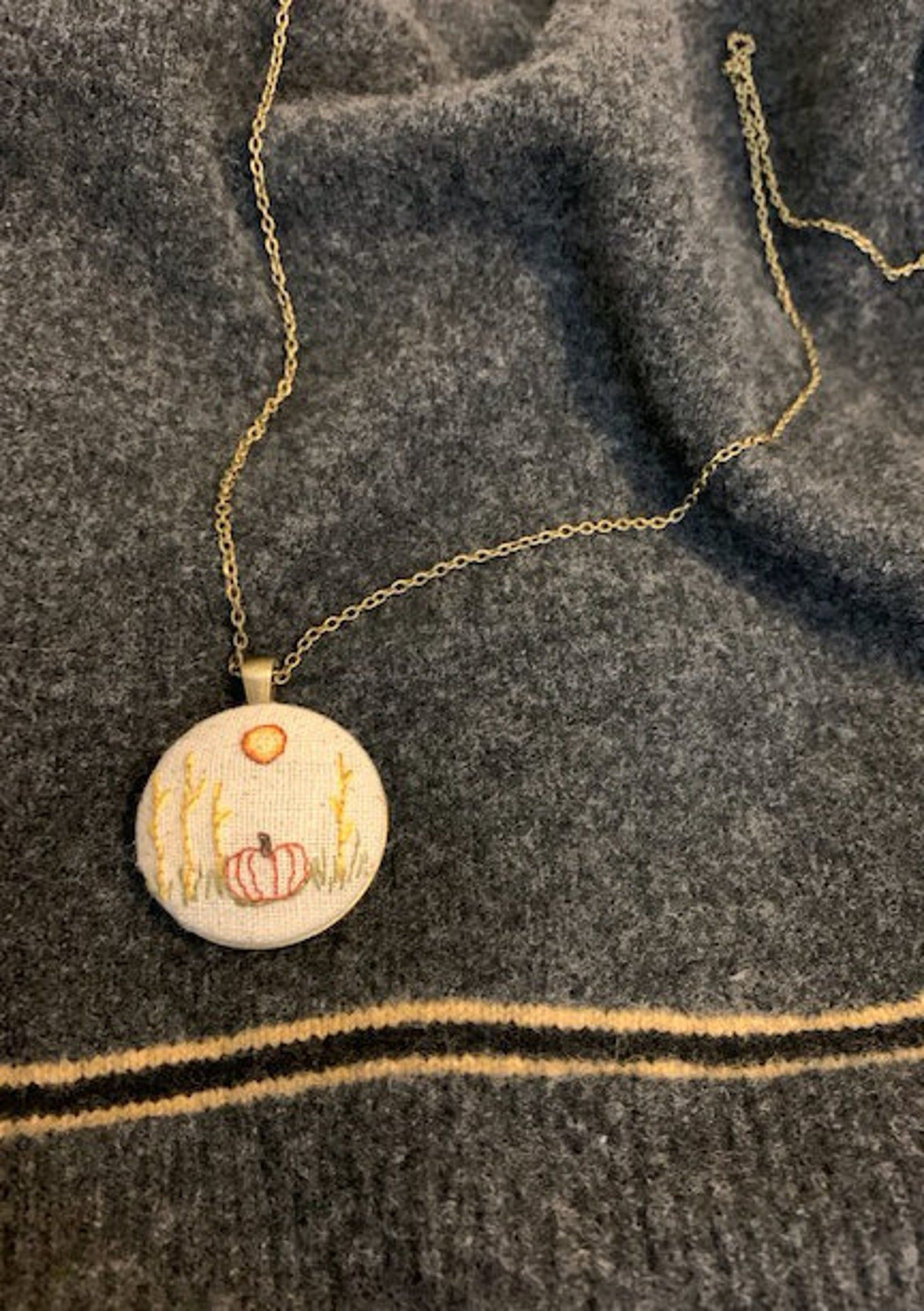 All pumpkin everything, including this mini embroidered pendant necklace featuring a pumpkin.