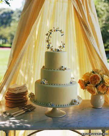 A sunny canopy parts to reveal a three-tiered fondant-covered cake. It is finished with an initial made of hand-painted sugar-paste flowers ... & Blooming Monogram.......A sunny canopy parts to reveal a three ...