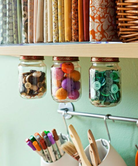 Snag storage solutions from all around the house. Small food jars can be affixed to the undersides of shelves to hold baubles without causing clutter: Screw lids from salvaged jars to shelves; then twist jars on. Raid your closet for a skirt hanger and use it to clip oversize scrapbooking papers. If you're working in a guest room or home office, closet-rod shelving and over-the-door shoe bags hold supplies out of sight when company calls.