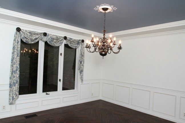 Remodel: Painted ceiling blue, painted over dark wood, added moulding on lower wall, tile 'wood' flooring, stencil and medallion above light, spray painted brass light