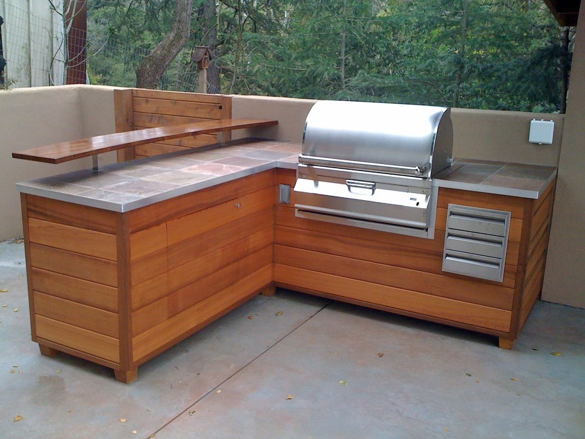 An outdoor barbeque island that looks like wooden for Outdoor kitchen cabinets