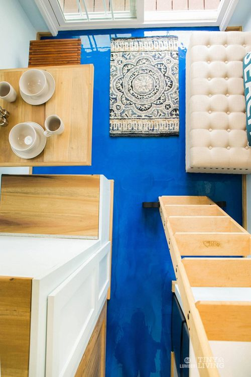 The blue epoxy floor in this tiny house is easy to maintain and adds a vibrant touch of color.