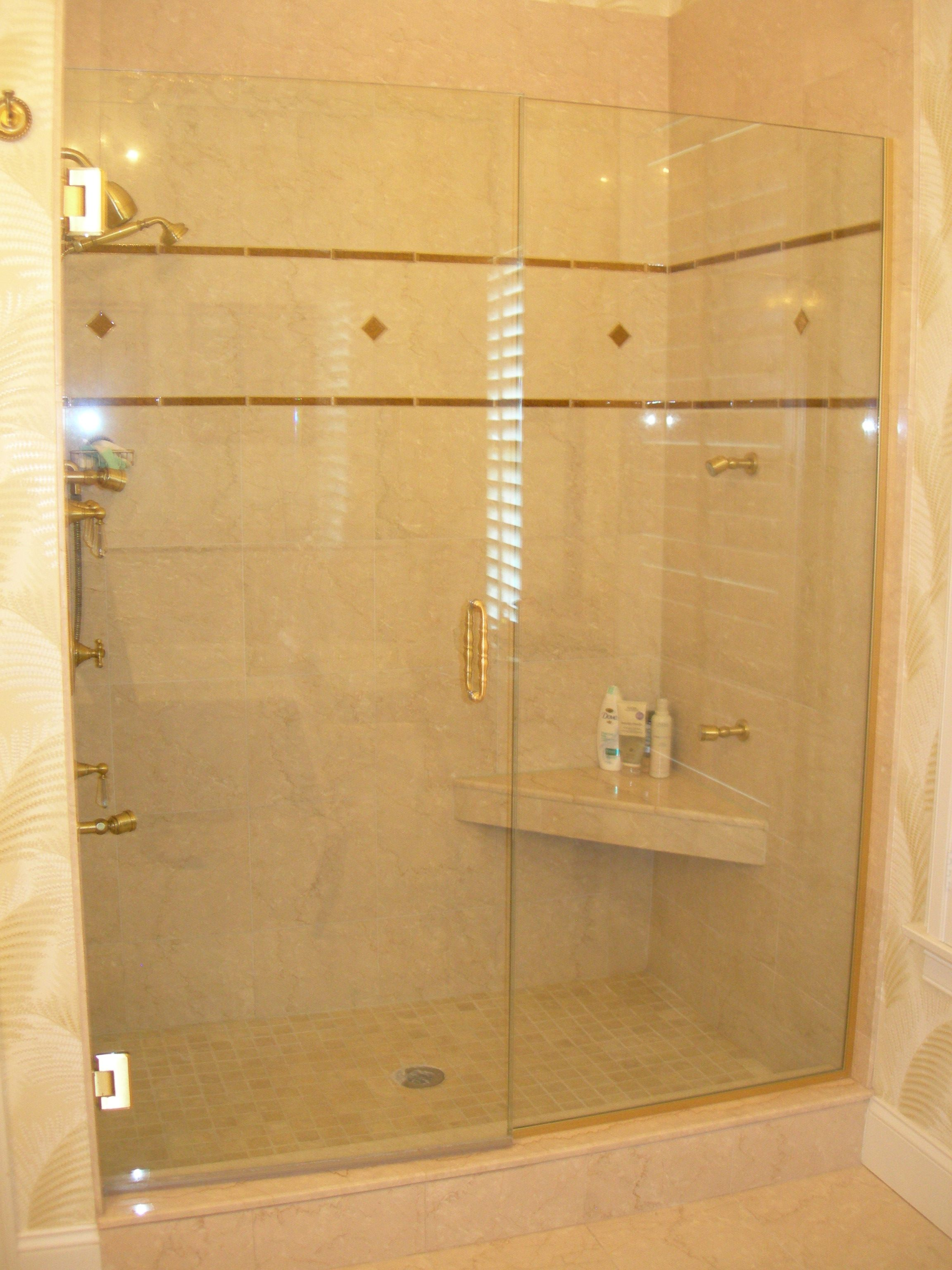 An over sized shower stall with a corner seat and marble and glass ...